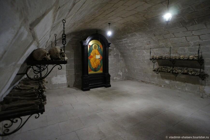 Здесь установлена икона Господа Вседержателя, по обе стороны от которой вдоль стен на деревянных полках покоятся кости наших давних и не столь давних предков...