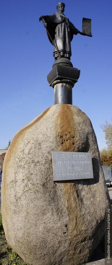 """На повороте к мосту через Волгу на огромном валуне стоит статная женская фигура. В правой руке у неё посох, в левой - свиток. Это Старица.  Её фигура изображена на гербе города с 1770 года.  """"В лето 1297 срублен бысть городок на Волзе ко Зубцову на Старице"""", - написано на табличке."""