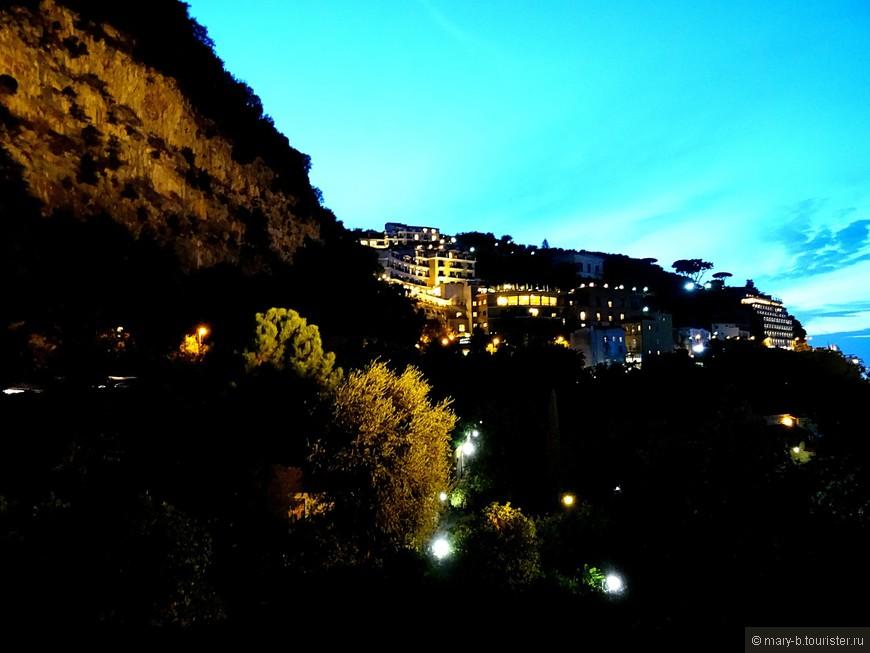 Вечерние огни района Капо-ди-Сорренто (верхний Сорренто) среди скал и силуэтов пиний