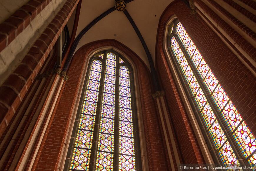 Огромные окна украшены витражами