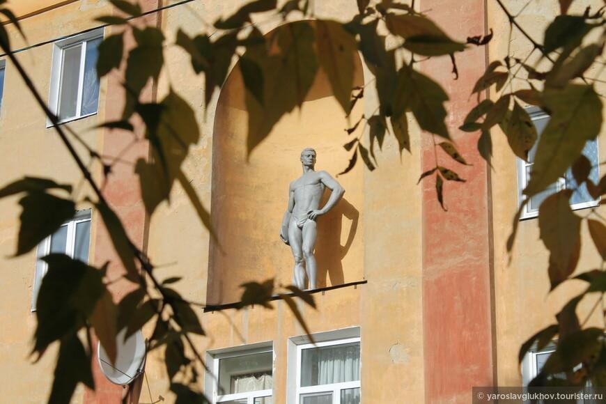 Скульптура мужчины в доме двестипяти в обрамлении золотых листьев.