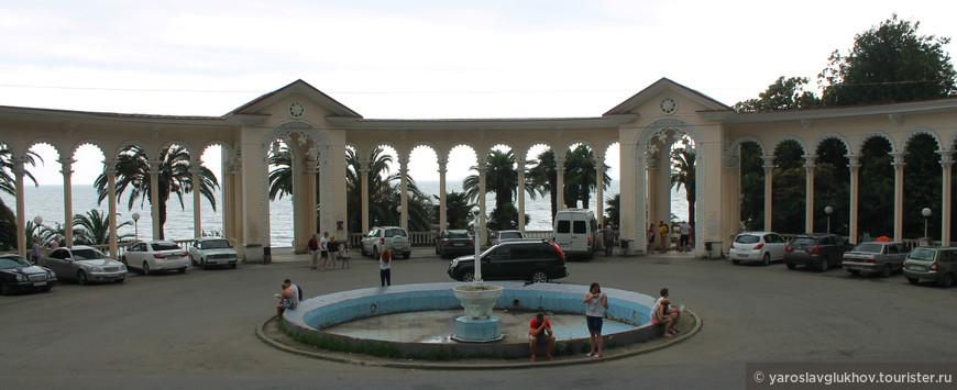 Колоннада — главная достопримечательность Гагры и один из символов всей Абхазии. Перед ней расположен неработающий фонтан, также слишком много машин припарковано рядом.