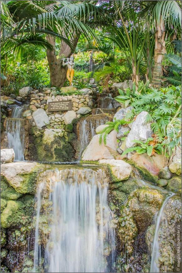 статуя играющего на флейте Кришны у малого водопада 10 футов (3,0 м).