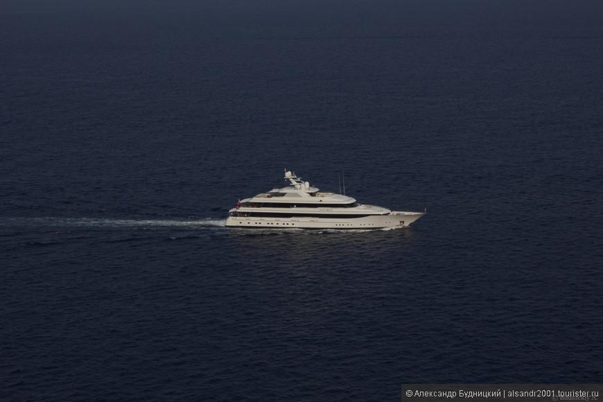 Рассекая волны, плывёт по морю белая яхта.