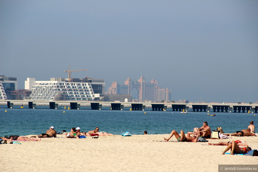 С пляжа хорошо видно отель Атлантис и еще какие-то строящиеся объекты. А вот лежать приходится под палящим солнцем.