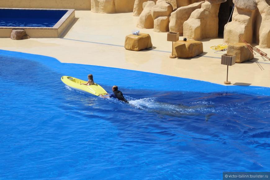 Мужчину, держащего лодку с ребенком, толкают двое дельфинов.
