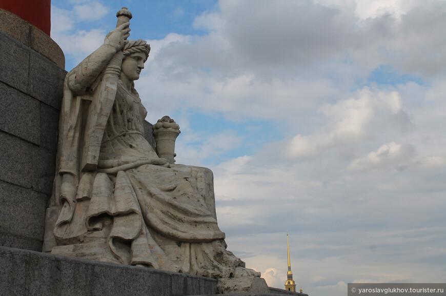 Статуя Волги на подножье Ростральной колонны, на заднем плане виднеется шпиль Петропавловского собора.