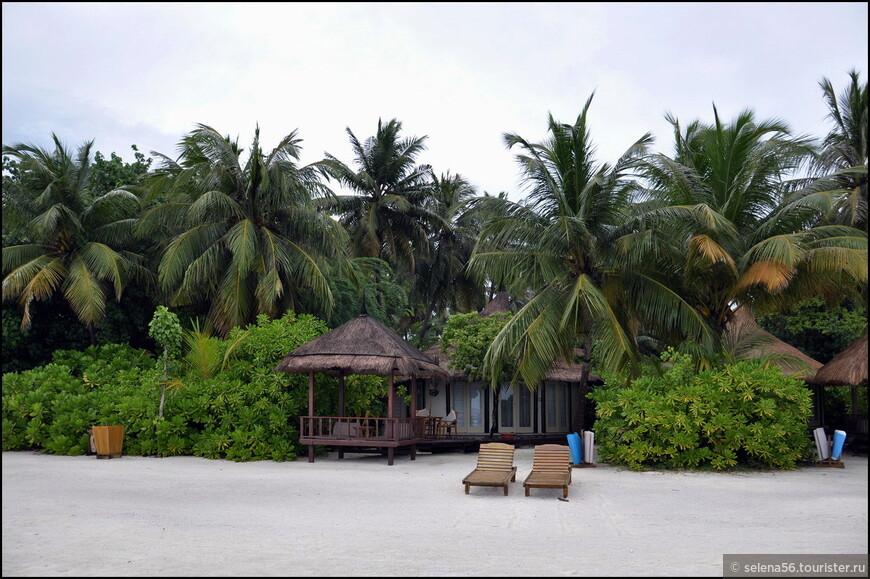 Вид на  пляжные бунгало и  беседку для отдыха.  Такого типа номера  расположены по всему периметру острова.