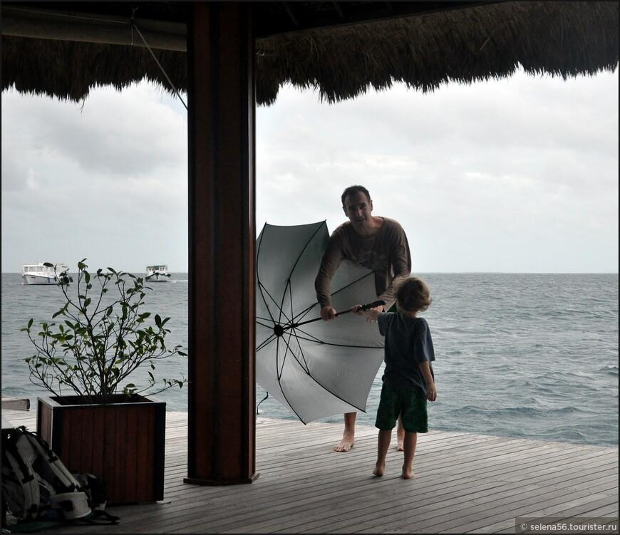 Начинался  дождь Поднялся сильный ветер на пирсе. Мальчика с  зонтом чуть не подхватило,мы предупредили его отца  взять зонт.