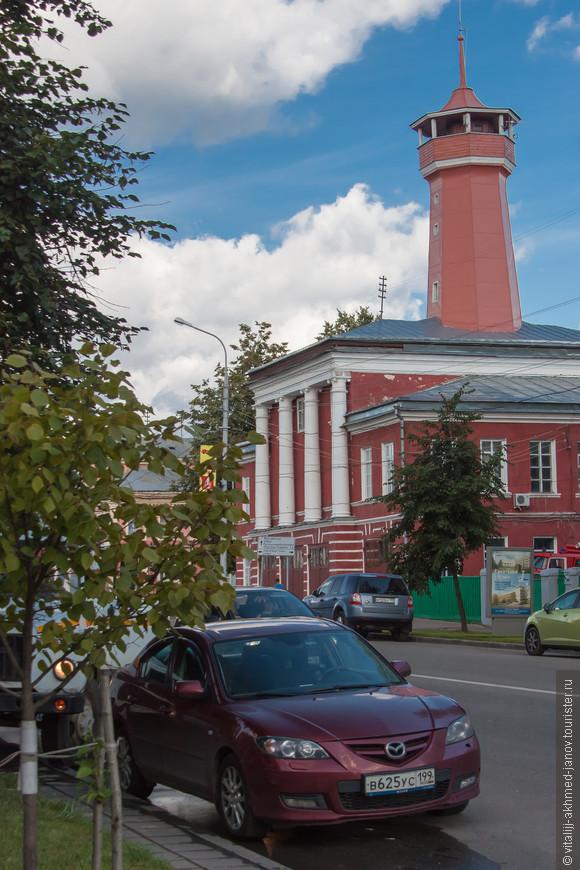 Пожарная часть  Пожарная часть в Угличе    Здание пожарной части на центральной улице города, рядом с центральной площадью, было построено в 1828-1831 годах. Судя по всему, строилось оно изначально не только для пожарной части: в помещениях располагались и пожарные со своими телегами, лошадьми, насосами, и полицейское управление (Городническое правление, как его тогда называли). Полицейское управление было упразднено в 1870 году, и здание осталось за пожарной командой.     Само здание построено в стиле классицизм с характерными для провинциальной Пожарная часть в Угличеархитектуры чертами: очень широко расставленными колоннами, капителями странной формы. Но в целом это ничуть не портит общего облика здания, на крыше которого стоит высокая каланча со смотровой площадкой. Первоначально в нижнем этаже было трое широких ворот для выезда пожарной команды; позднее в правом крыле на месте окон прорубили четвертые. Весь нижний этаж украшен частой рустовкой.     Пожарная часть по-прежнему, как и почти два столетия назад, выполняет свои функции, хотя за ее воротами стоят уже не сытые кони с бочками на телегах, а красные автомобили, а на пожарных больше не увидишь сияющих медных касок, которым на смену пришли более надежные шлемы. Да и в каланче нет такой необходимости – гораздо быстрее обо всем сообщают по телефону. Но едва ли кто-либо рискнет сказать, что каланчу следует снести. Она, как и все здания на старых улицах города, давно стала неотъемлемой частью угличского пейзажа. (http://uglichru.ru/Arhitect/poz_chast.htm)