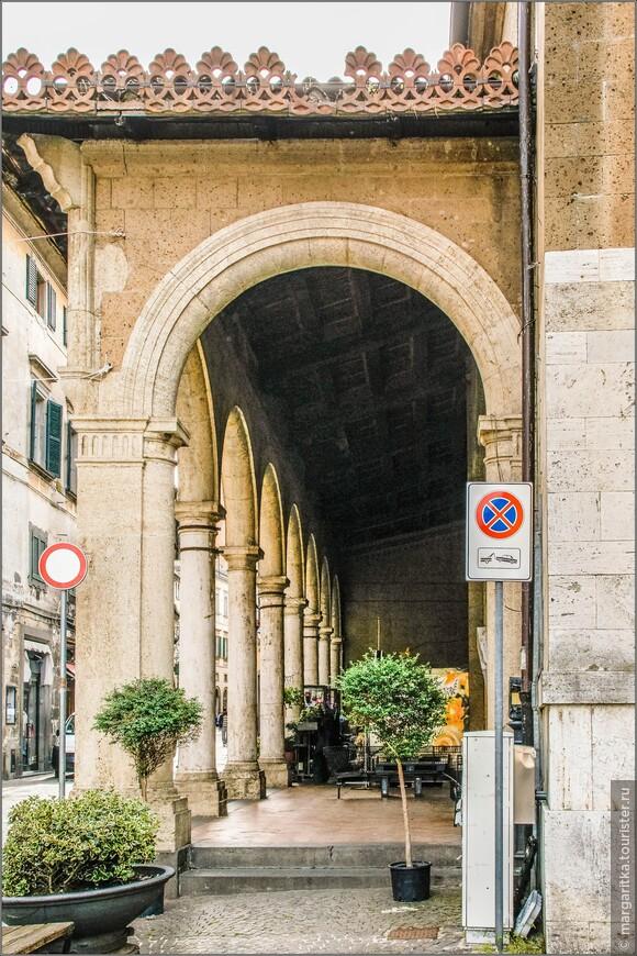 Это одна из древнейших церквей города, первый храм на этом месте был воздвигнут на руинах языческого сооружения этрусской эпохи в 6 веке. В это время из Больсены в Орвието была перенесена резиденция епископа, что, по всей видимости, стало причиной строительства новой крупной базилики. Остатки напольной инкрустации и мозаик этой древней раннехристианской церкви сегодня можно видеть в подземной крипте.( справа 12-гранная колокольня храма св. Андрея, а слева вот эта анфилада с колоннами)