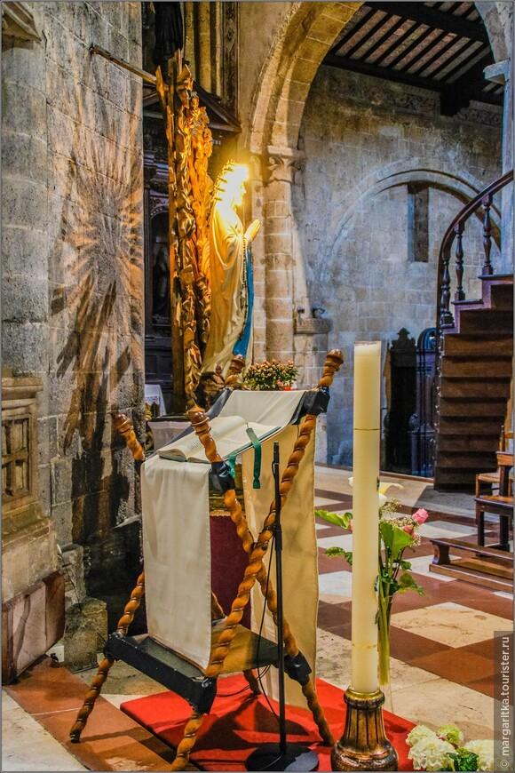 свеча. аналой с открытой библией на фоне фигуры Девы Марии