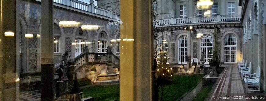 """Через стекло мы заглянули во внутренний дворик. Это - жемчужина здания. Он так и называется - """"Schmukgarten""""  - драгоценный садик. Расписные стены в нём украшают многочисленные портреты знаменитостей, бывавших здесь."""