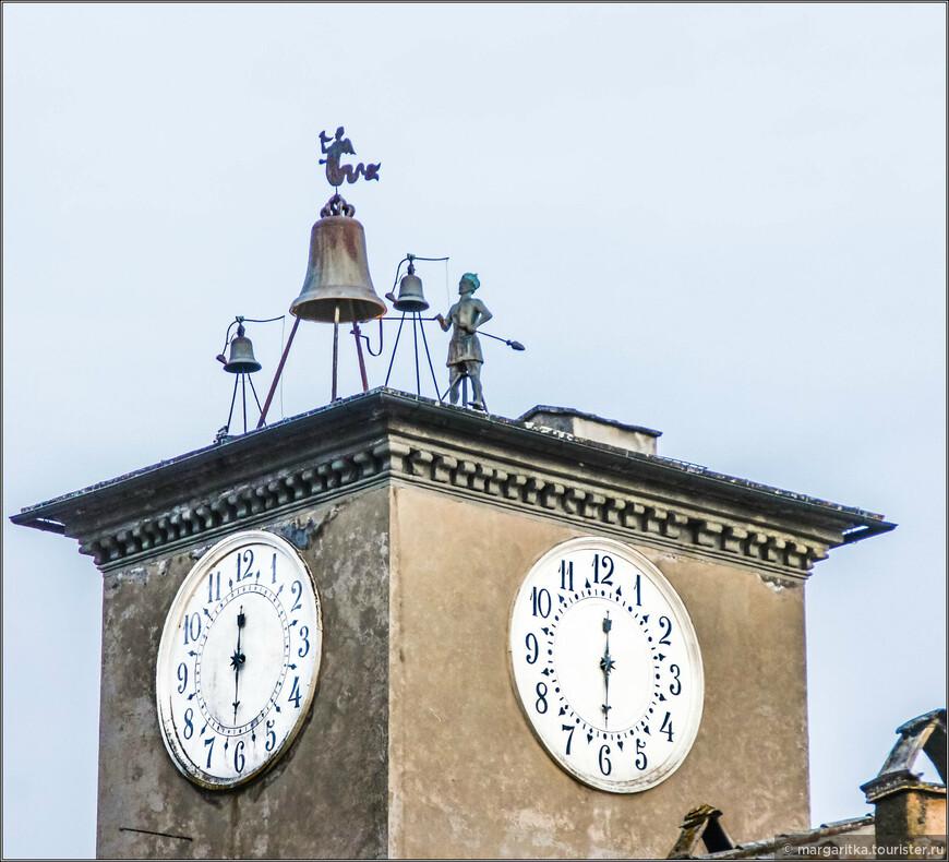 Башня с часами высотой 65 м. получила имя Маурицио вчесть своего  мастера. Была построена в 1351г.  Её крышу венчает бронзовая композиция изстатуи звонаря, который держит в руках молоток и ударами по большому колоколу он отбивает каждый час. По обеим сторонам от большого колокола расположены два колокола по меньше. Их молоточки тоже меньшего размера отбивают каждую четверть часа.