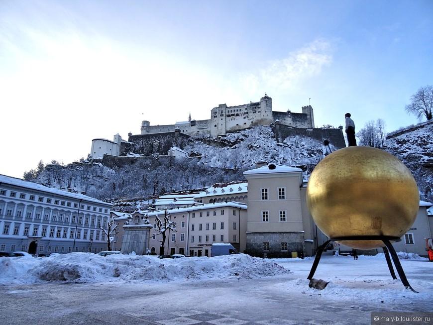 """Вид на крепость Хоэнзальцбург с площади Капительплац. Человек на золотом шаре - это памятник Паулю Фюрсту, придумавшему рецептуру конфет """"Моцарт""""."""