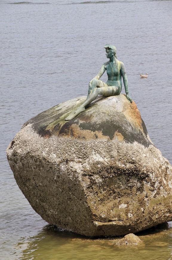 """К созданию этого памятника подтолкнул камень, выглядывающий из воды. Напомнил он тот, на котором сидит всем известная датская Русалочка. И решил венгерский скульптор И. Имреди, живший последние годы жизни именно в Ванкувере, создать свою девушку на камне. Прообразом послужила его жена. Издалека скульптура и правда очень напоминает Русалочку и только подойдя поближе можно рассмотреть и ласты, и гидрокостюм. Официальное имя у памятника """"Девушка в гидрокостюме""""."""