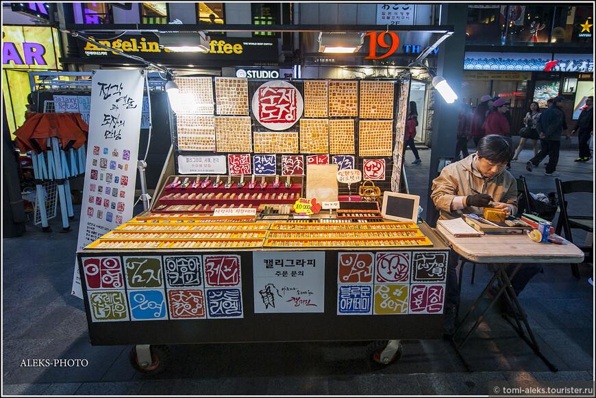 Разбавим виды еды. Здесь мы видим мастера по изготовлению маленьких печатей. Видимо, это дело не плохо процветает в Корее. Таким мастерских прямо на улице мы видели много...