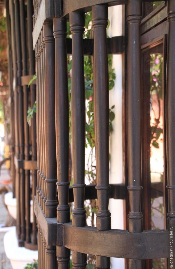 Решетки на окнах не чугунные и не аллюминивые - не к лицу это Картахене. Теплое, темное дерево, пропахшее солнцем и морским ветром, украшает окна старых домов...