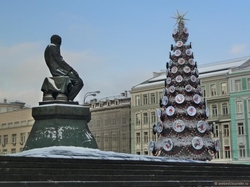 Замёрзший памятник Ф. Достоевскому перед новогодней ёлкой.