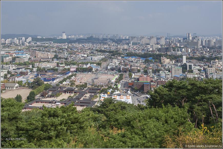 Ландшафт города преимущественно, холмистый. Южная Корея, вообще, находится на полуострове, где сплошные горные массивы. Отсюда столько ручьев, которые текут с гор. И корейская традиция - гулять вдоль ручьев. Но сейчас мы гуляем по холмам в крепости Хвасон. Вот внизу по серым квадратикам крыш мы видим Хвасон Хенгун (행궁) - временный королевский дворец, где король останавливался 13 раз. Заходить в него мы не будем, так как уже видели в Сеуле нечто подобное. Все дворцы Кореи примерно одинаковые. Отличается лишь ландшафт вокруг них.