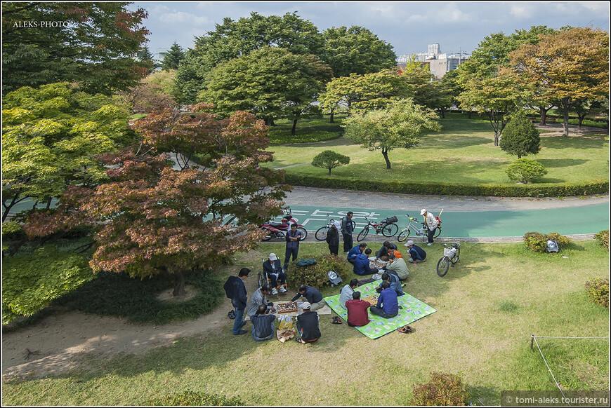 Корейцы - большие любители что-то делать коллективно. В этом они полностью схожи с китайцами. Вот тут мы видим пикничок на обочине. Народ играет в шашки. Кто-то приехал на велосипедах. Велосипеды - для корейцев - любимый вид отдыха. Много велодорожек проложены как раз в подобных этому комплексу парках и вдоль ручьев и рек.