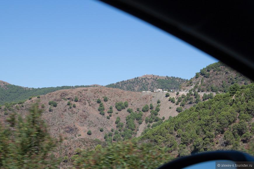 Дорога вьется все выше - и даже на верху дальнего холма видно какое-то строение и подъездную дорогу.