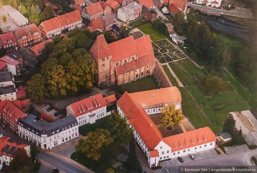 """Вид на сохранившиеся здания монастыря. На переднем плане, перед церковью - """"длинный дом""""."""