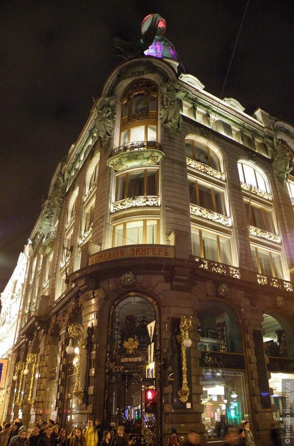 Это красивое шестиэтажное здание с мансардой и стеклянной башенкой находится в самом центре Санкт-Петербурга — на Невском проспекте и имеет два вполне официальных названия. Первое — Дом Зингера, оно получило по имени всемирно известной фирмы по производству швейных машинок. В самом начале XX века, когда архитектором Павлом Сюзором был построен этот шедевр в стиле барокко, здесь распологался один из многих офисов заокеанской компании. Дела у Зингера шли хорошо, а огромный российский рынок обещал сказочные дивиденды. Недаром, на башенке дома был установлен огромный глобус. Держат его две фигуры и как всегда — это женщины. Для них прежде всего предназначалась продукция Зингера и они же поддерживали его мир. Но мир оказался хрупким. После Октябрьской революции 1917 года дом национализировали и в нём поселились другие ценности.