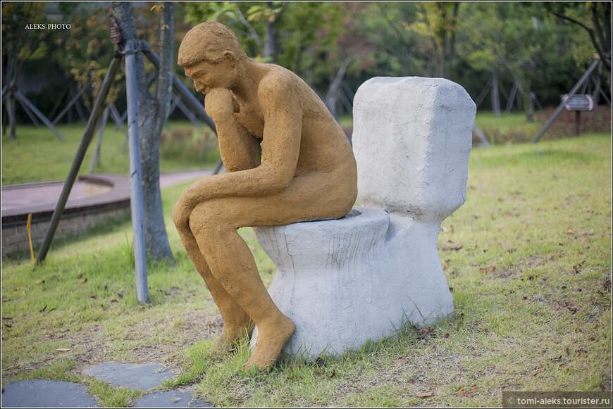 """Теперь, чтобы как-то разнообразить нашу экскурсию в Мир Туалетов, давайте перемежать материалы из интерьера музея со скульптурами, составляющими экспозицию в мини-парке, прилегающем к зданию. Иначе от необычных рисунков корейской детворы у нас запестрит в глазах.  Выходим во двор. Эта скульптура называется """"Мыслитель сидит на унитазе"""". Образно!"""