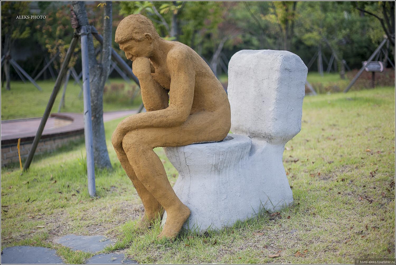 """Теперь, чтобы как-то разнообразить нашу экскурсию в Мир Туалетов, давайте перемежать материалы из интерьера музея со скульптурами, составляющими экспозицию в мини-парке, прилегающем к зданию. Иначе от необычных рисунков корейской детворы у нас запестрит в глазах.  Выходим во двор. Эта скульптура называется """"Мыслитель сидит на унитазе"""". Образно!, Околотуалетная тема по-корейски (Южная Корея)"""