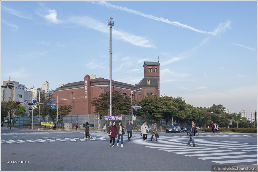 Дальше, от станции метро, идем пешком. В Южной Корее мы много ходили пешком, чтобы увидеть как можно больше. Вот на заднем плане мы видим христианскую церковь, которых очень много в Южной Корее. Видите справа на башне крест? Дорогу на этом перекрестке можно переходить по диагонали. Раньше для нас это было экзотикой. Сейчас и в городе, где мы живем, вводится такая система. Вот только есть одно отличие - дороги в Южной Корее очень широкие. Может, потому, что города современные.